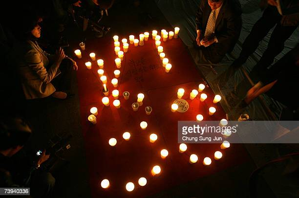 South Koreans participate in a candle light vigil for the victims of the Virginia Tech University shootings in front of city hall on April 21 2007 in...