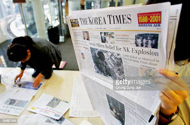 South Koreans read newspaper reports on North Korea's train explosion on April 23 2004 in Seoul South Korea Two fuel trains collided and caused a...