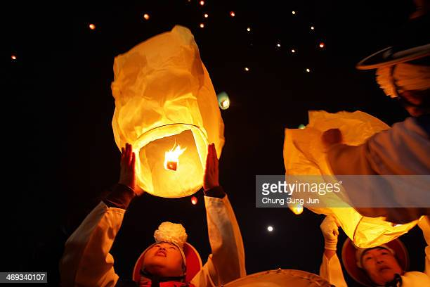 South Koreans release paper hot air balloon for good luck during 'Jwibulnoli' a South Korean folk game on February 14 2014 in Yongin South Korea The...