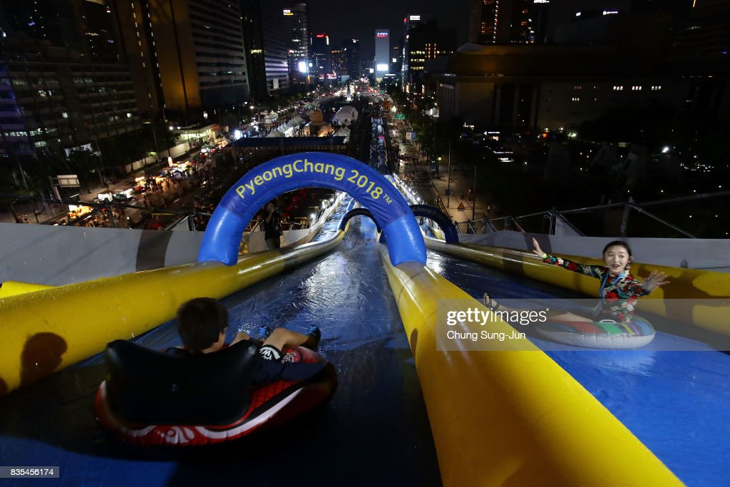 South Koreans slide down on an inflatable ring during the 'Bobsleigh In the City' on August 19, 2017 in Seoul, South Korea. The 22-metre-high 300-metre-long water slider has been set up in the central Seoul to promote upcoming PyeongChang Winter Olympics.