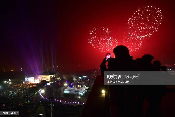 South Koreans take pictures of fireworks during a countdown event to celebrate the New Year at Imjingak peace park in the border city of Paju near...