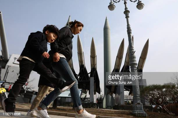 South Koreans walk past replicas of a North Korean ScudB missile and South Korean Nike missile at the Korean War Memorial on February 28 2019 in...