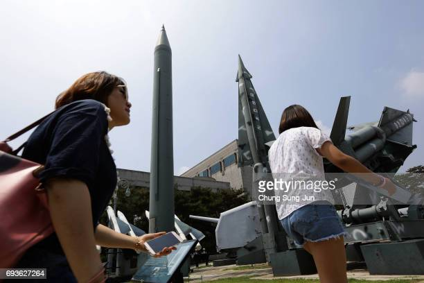 South Koreans walk past replicas of a North Korean ScudB missile and South Korean Nike missile at the Korean War Memorial in Seoul on June 8 2017 in...