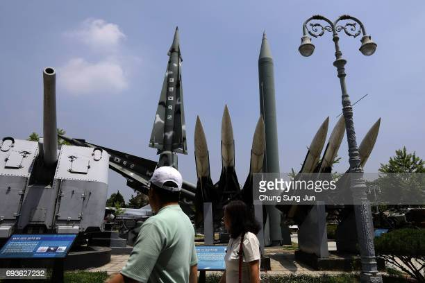 South Koreans walks past replicas of a North Korean ScudB missile and South Korean Nike missile at the Korean War Memorial in Seoul on June 8 2017 in...