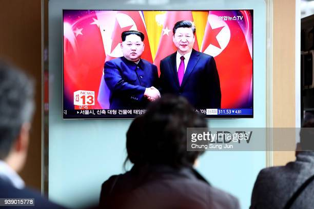 South Koreans watch a television broadcast reporting the North Korean leader Kim Jongun meet Chinese President Xi Jinping at Seoul Railway Station on...