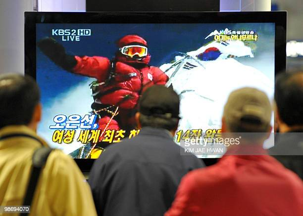 South Koreans watch live television as Oh EunSun plants her national flag on the summit of Annapurna an 8091metre mountain in Seoul on April 27 2010...