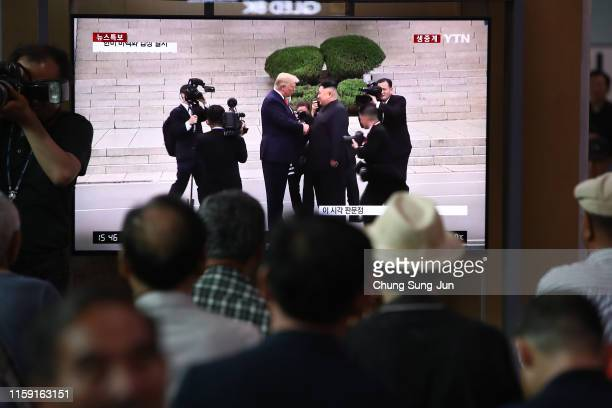 South Koreans watch on a screen reporting on the North Korean leader Kim Jong Un meeting with US President Donald Trump at the Seoul Railway Station...