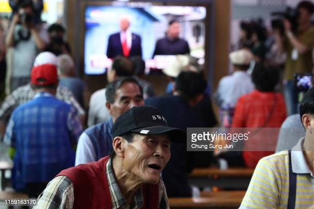 South Koreans watch on a screen reporting on the North Korean leader Kim Jong Un meeting with U.S. President Donald Trump at the Seoul Railway...