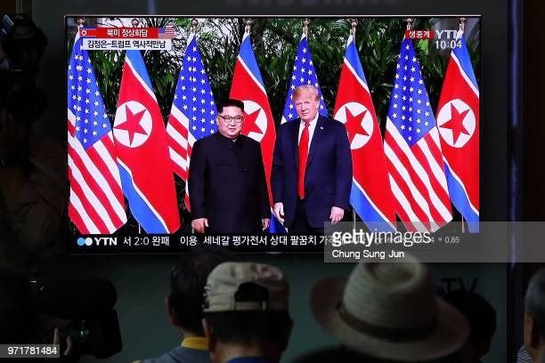 South Koreans watch on a screen reporting on the US President Trump meeting with North Korean leader Kim Jongun at the Seoul Railway Station on June...