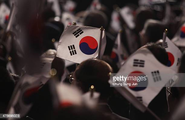 South Koreans wave national flags during the 95th Independence Movement Day ceremony at Sejong Art Center on March 1 2014 in Seoul South Korea South...