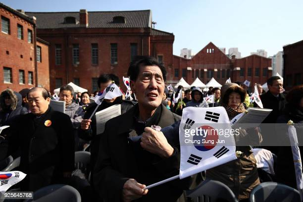 South Koreans wave national flags during the 99th Independence Movement Day ceremony at Seodaemun Prison History Hall on March 1, 2018 in Seoul,...