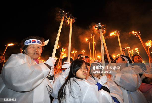 South Koreans wearing traditional costumes carry torches in their hands to celebrate the March 1 Independence Movement Anniversary in Cheonan, 90 kms...