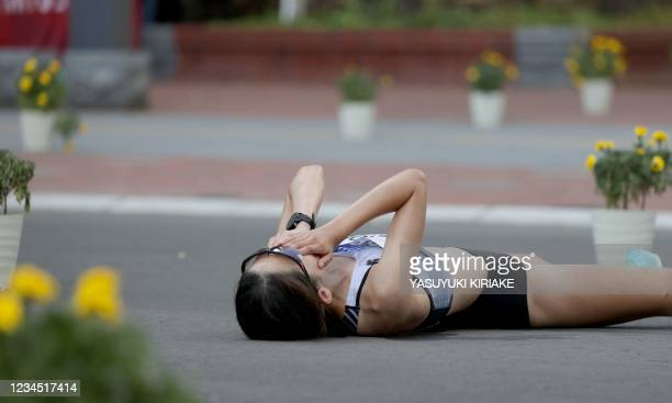 South Korea's Choi Kyungsun covers her face as she falls on the street while competing in the women's marathon final during the Tokyo 2020 Olympic...
