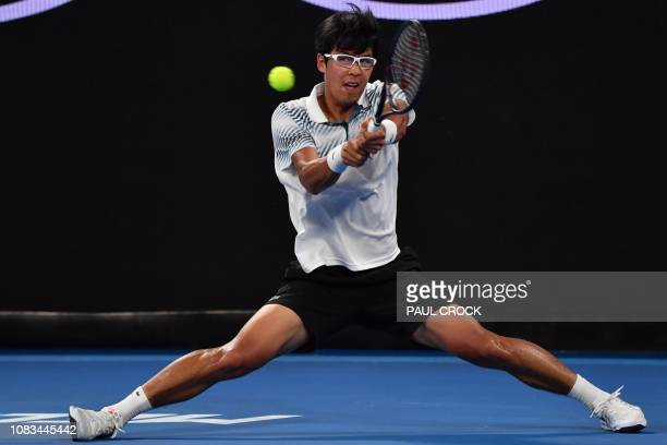 South Korea's Chung Hyeon hits a return against France's Pierre-Hugues Herbert during their men's singles match on day four of the Australian Open...