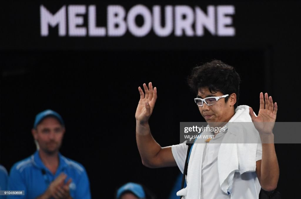 TOPSHOT - South Korea's Chung Hyeon reacts after retiring against Switzerland's Roger Federer during their men's singles semi-finals match on day 12 of the Australian Open tennis tournament in Melbourne on January 26, 2018. /