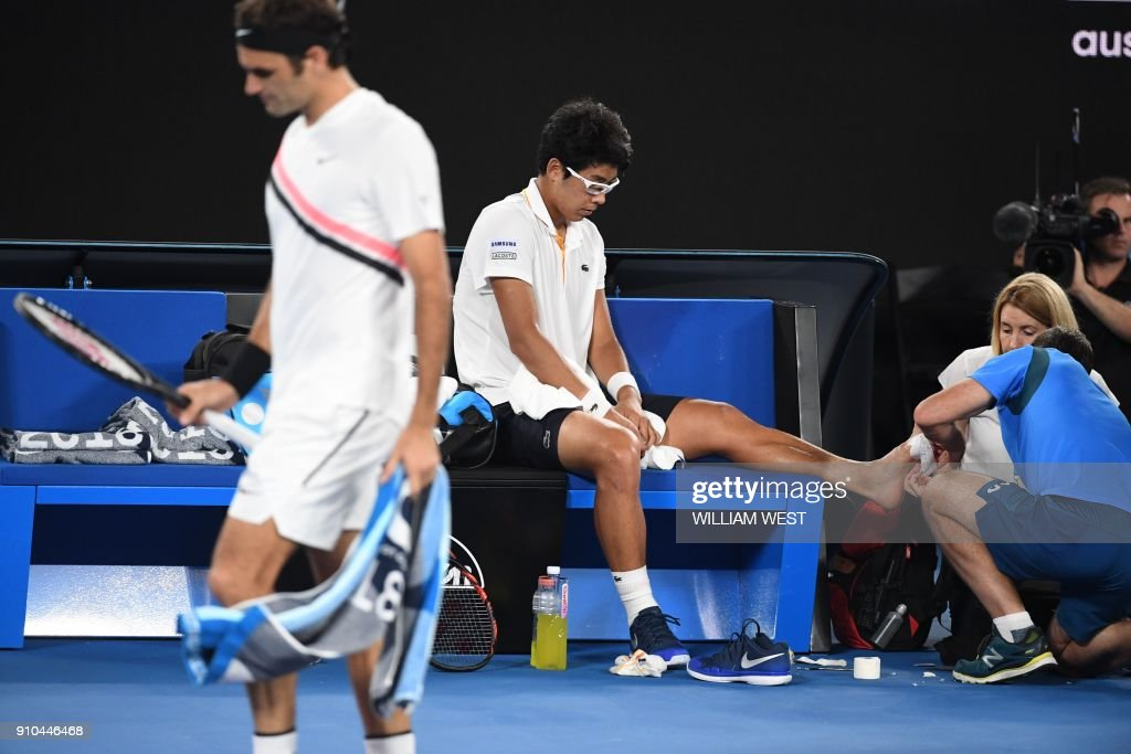 TOPSHOT - South Korea's Chung Hyeon receives medical attention against Switzerland's Roger Federer (L) during their men's singles semi-finals match on day 12 of the Australian Open tennis tournament in Melbourne on January 26, 2018. /