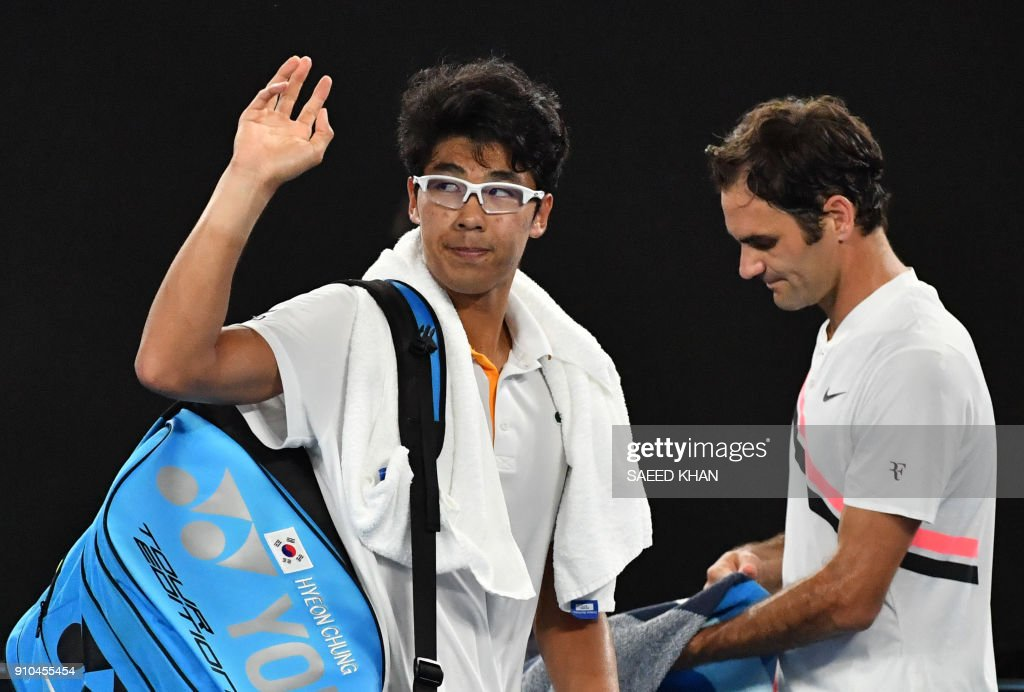 South Korea's Chung Hyeon (L) waves to the crowd after retiring against Switzerland's Roger Federer during their men's singles semi-finals match on day 12 of the Australian Open tennis tournament in Melbourne on January 26, 2018. /