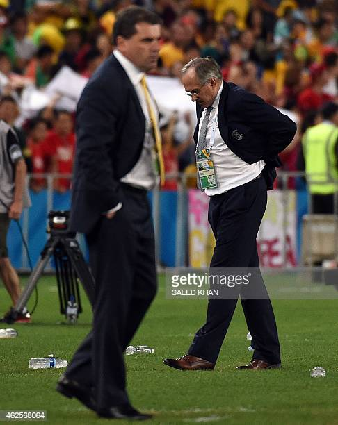South Korea's coach Uli Stielike walks past Australian counterpart Ange Postecoglou during the AFC Asian Cup football final between South Korea and...