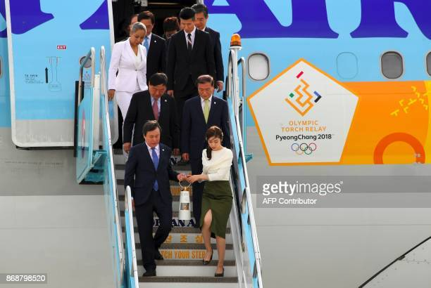 South Korea's Culture Sports and Tourism Minister Do JongWhan and former figure skating champion Yuna Kim carry the Olympic flame upon its arrival at...