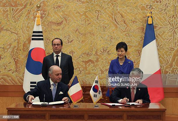 South Korea's Culture Sports and Tourism Minister Kim JongDeok and French Minister of Foreign Affairs Laurent Fabius sign a document as South Korean...