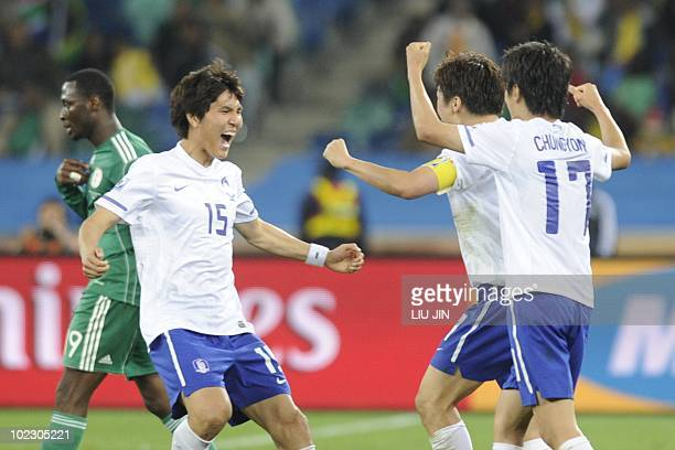 South Korea's defender Kim DongJin South Korea's midfielder Park JiSung and South Korea's midfielder Lee ChungYong celebrate after their Group B...