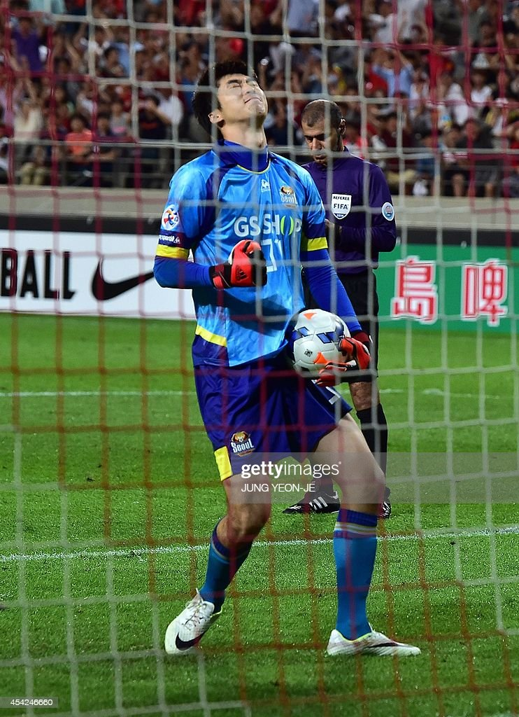 South Korea's FC Seoul goalkeeper Yu Sang-Hun (C) reacts as he blocked a spot kick of South Korea's Pohang Steelers in the penalty shootout during the AFC Champions League quarter final football match in Seoul on August 27, 2014. FC Seoul beat Pohang Steelers 3-0 on spot kicks after a tie.