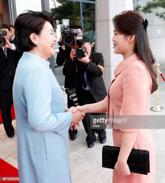South Korea's first lady Kim Jungsook shakes hands with North Korean first lady Ri Solju upon arrival at the Peace House on April 27 2018 in...