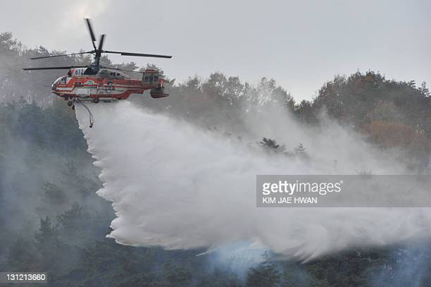 South Korea's forest service helicopter drops water during a forest firefighting joint drill in Chungju on November 3 2011 The drill is part of a...