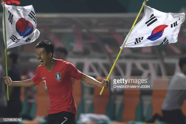South Korea's forward Heung Min Son celebrates after defeating Japan during the men's football gold medal match at the 2018 Asian Games in Bogor on...