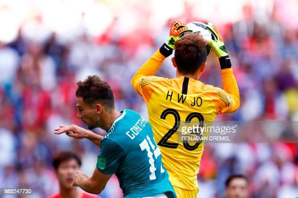 South Korea's goalkeeper Cho Hyunwoo catches the ball ahead of Germany's midfielder Leon Goretzka during the Russia 2018 World Cup Group F football...