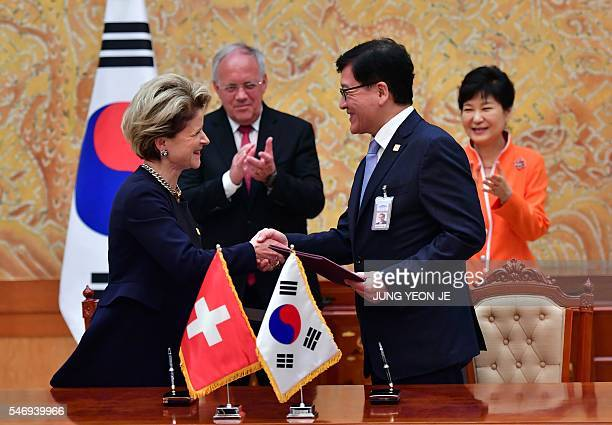 South Korea's Health and Welfare Minister Chung ChinYoub exchanges documents with Swiss State Secretary for Economic Affairs MarieGabrielle...