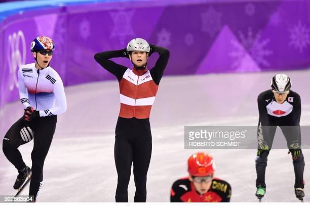 South Korea's Hwang Daeheon Latvia's Roberts Janis Zvejnieks China's Wu Dajing and Japan's Keita Watanabe reacts after competing in the men's 500m...
