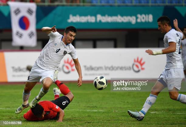 South Korea's Hwang Hee Chan fights for the ball with Uzbekistan's Akramjon Komilov during the quarterfinal men's football match between Uzbeskitan...