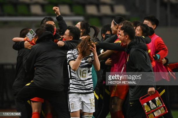 South Korea's Jang Sel-gi reacts as China's team celebrate their victory during the qualifying play-off second leg women's football match for the...