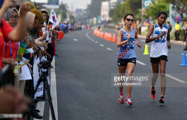 South Korea's Jeon Yeongeun and India's Soumya Baby compete in the women's 20km walk race competition during the 2018 Asian Games in Jakarta on...