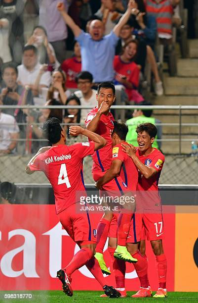 South Korea's Ji DongWon celebrates a goal with teammates an own goal by China during the World Cup 2018 football qualification match between South...
