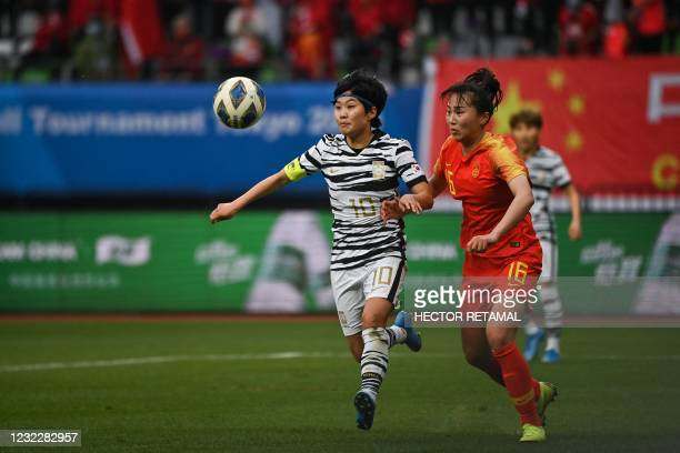 South Korea's Ji So-yun and China's Wang Xiaoxue compete for the ball during the qualifying play-off second leg women's football match for the Tokyo...