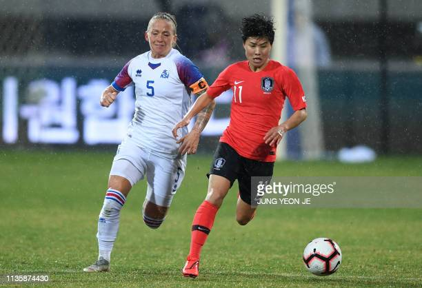 South Korea's Ji Soyun fights for the ball with Iceland's Jonsdottir Gunnhildur Yrsa during a women's friendly football match in Chuncheon on April 9...