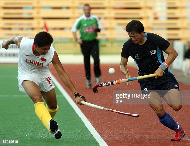 South Korea's Jin Kyung Min controls the ball as China's Guo Zhong Qiang chases during their semifinal match at the Asia Cup field hockey tournament...