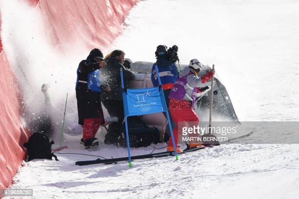 TOPSHOT South Korea's Jung Donghyun smashes into a group of volunteers and camera crew after falling while competing in the Men's Giant Slalom at the...