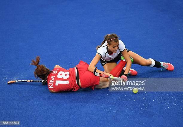 South Korea's Kim Bomi falls over Germany's Selin Oruz during the women's field hockey Germany vs South Korea match of the Rio 2016 Olympics Games at...
