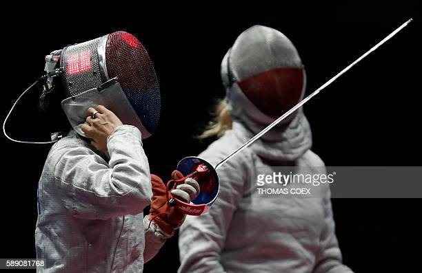 South Korea's Kim Jiyeon reacts next to Poland's Aleksandra Socha after winning the womens team sabre placement 56 bout between Poland and South...