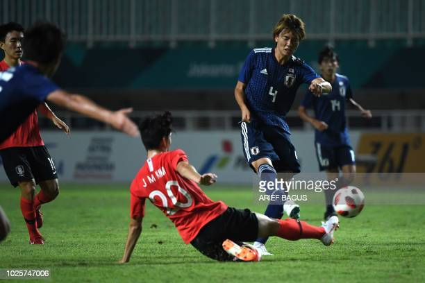 South Korea's Kim Jungmin fights for the ball with Japan's Kou Itakura in the men's gold medal football match at the 2018 Asian Games in Bogor on...