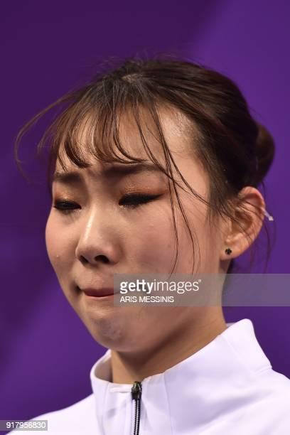 South Korea's Kim Kyueun reacts after competing with partner South Korea's Alex Kang Chan Kam in the pair skating short program of the figure skating...