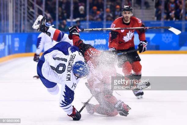 TOPSHOT South Korea's Kim Sangwook and Canada's Mat Robinson clash in the men's preliminary round ice hockey match between Canada and South Korea...