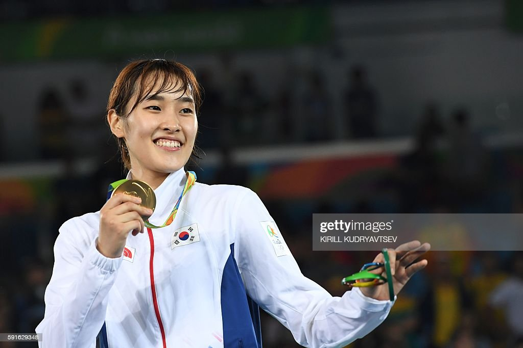 South Korea's Kim Sohui poses with her gold medal on the podium after the womens taekwondo event in the -49kg category as part of the Rio 2016 Olympic Games, on August 17, 2016, at the Carioca Arena 3, in Rio de Janeiro. / AFP / Kirill KUDRYAVTSEV