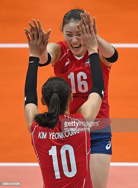 South Korea's Kim Yeon Koung celebrates with South Korea's Bae Yoo Na after winning a point during the women's qualifying volleyball match between...