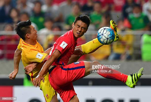 South Korea's Koo JaCheol fights for the ball with China's Ren Hang during their 2018 World Cup qualifying football match in Seoul on September 1...