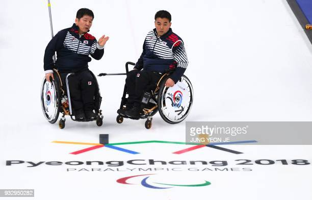 South Korea's Lee Dongha and Cha Jaegoan talk during the wheelchair curling bronze medal game between South Korea and Canada at the Gangneung Curling...