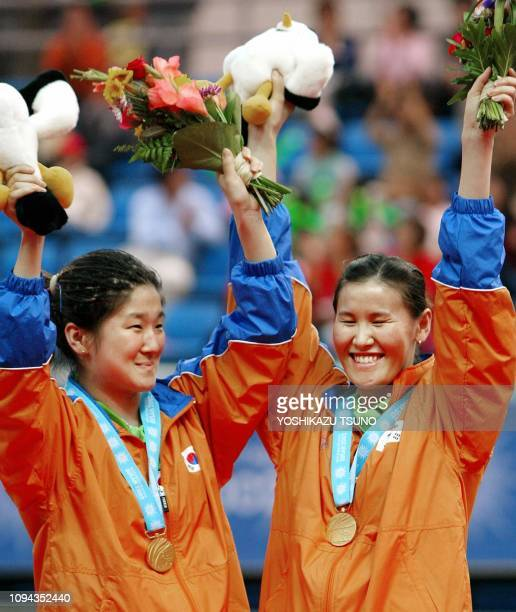 South Korea's Lee EunSil and Seok EunMi wave flower bouquets after receiving gold medals in the women's doubles table tennis final at the 14th Asian...